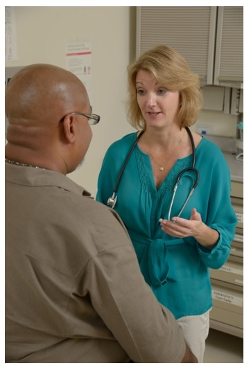 Actual photo of nurse in green shirt talking to a patient in a brown shirt