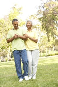 A photo of an older man and woman walking in a park.