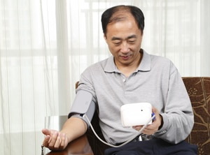 A photo of a man checking his blood pressure.