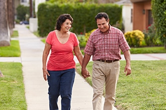 Smiling couple walking on the sidewalk holding hands.