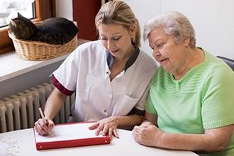 Una proveedora de atención médica comparte información con una mujer en su casa.