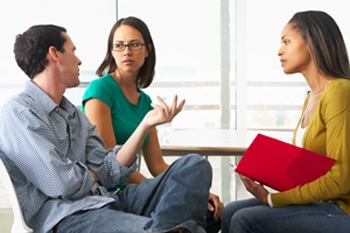 A photo of a man and a woman speaking with a genetics counselor.