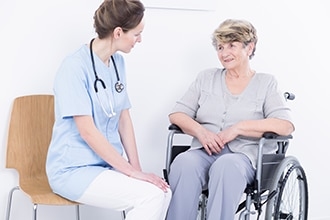 Health care provider talking with a woman in a wheelchair.