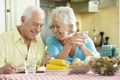 A photo of a man and a woman sitting at a table and eating a healthy meal