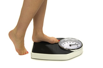 Close up of a person stepping onto a scale to weigh herself.