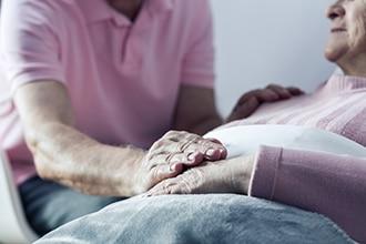 Un hombre consolando a una persona que está reclinada bajo unas mantas.