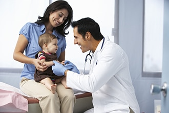 Mother holding an infant while a doctor performs a physical exam
