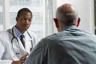 Männlicher Doktor, der mit männlichem Patienten spricht.