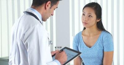 Doktor, der mit einem Patienten spricht.