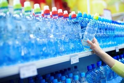 Eine Person, die in Flaschen abgefülltes Wasser in einem Speicher wählt
