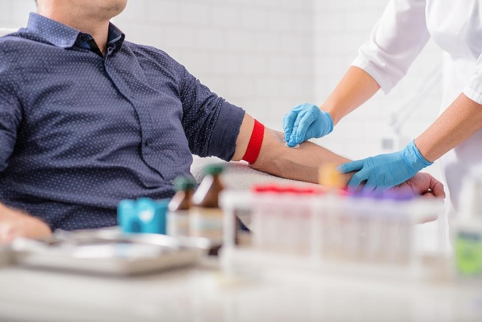 Health care professional preparing to take a blood sample from a patient.