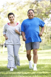 An overweight couple walking outdoors.