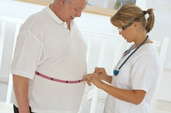 Health care professional measuring the waist of a man who is obese.