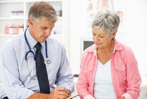 Doktor, der mit einem Patienten spricht und Kenntnisse nimmt.
