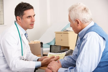 Male doctor talking with an older male patient.