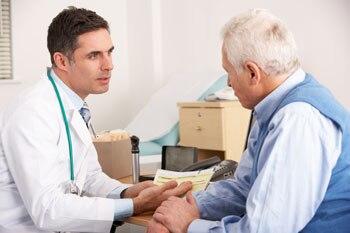 Männlicher Doktor, der mit einem älteren männlichen Patienten spricht.