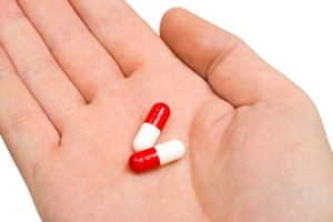 Two medicine capsules in the palm of a hand.