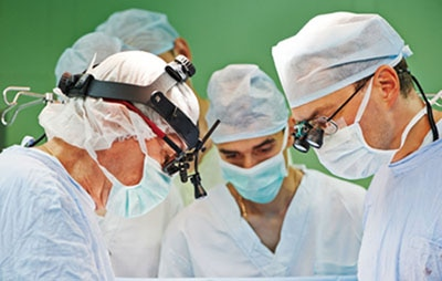 Surgeons with surgical caps, masks, and gowns looking down during surgery.