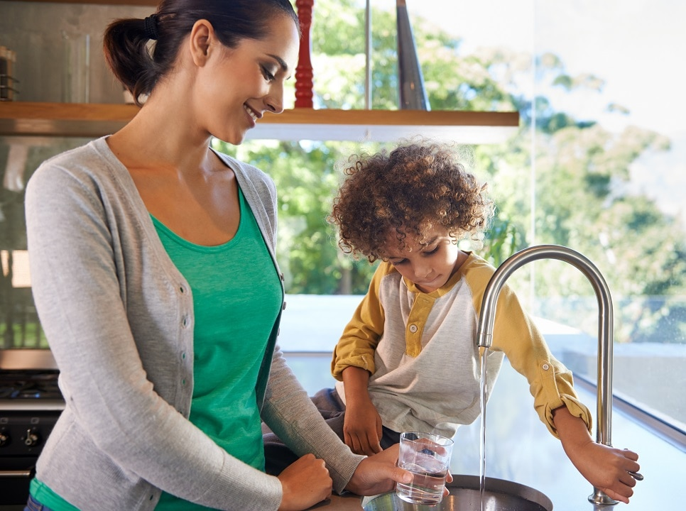 Mother with her young son getting a glass of water from a kitchen faucet.