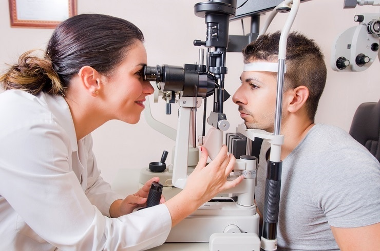 Doctor using a slit lamp to examine a patient's eyes.