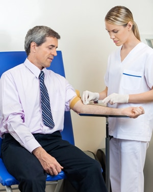 A health care professional taking a blood sample from a patient.