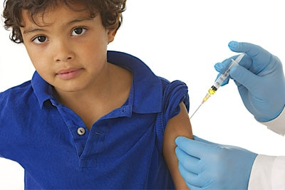 Doctor giving vaccine shot to small child.