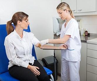 Ein Gesundheitspflegefachmann, der eine Blutprobe von einem Patienten nimmt.