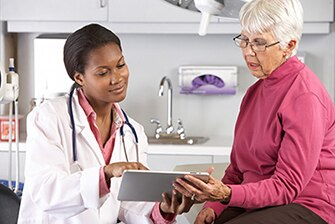 A health care professional reviewing medical records with a female patient