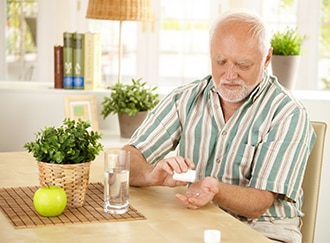 A man seated taking oral medicine with water.