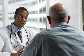 A health care professional listens to a male patient.