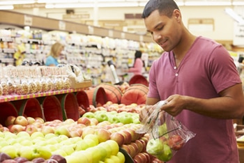 A man packing apples into a bag at the supermarket.