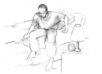 Male getting out of his bed, next to him a bed-side table with lamp.