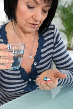 A woman with medicines in her hand and a glass of water