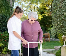 A care giver helping an elderly woman walk