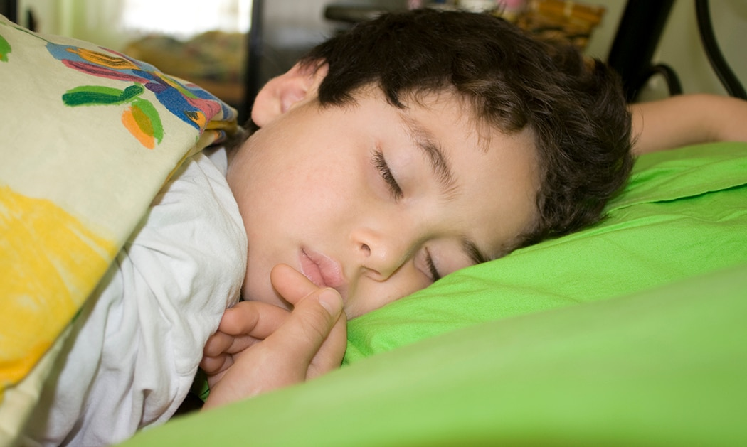 Boy sleeping under colorful blanket.