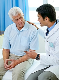 Male doctor conversing with a male patient.