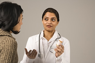 A young woman talks with a health care professional who is wearing a stethoscope.