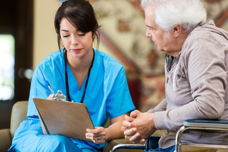 A healthcare professional sits with a patient, filling out a medical form.