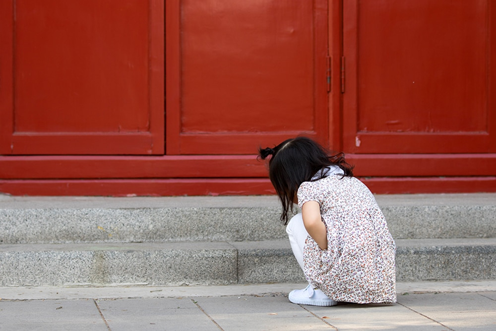 Young girl squatting to avoid leaking urine.