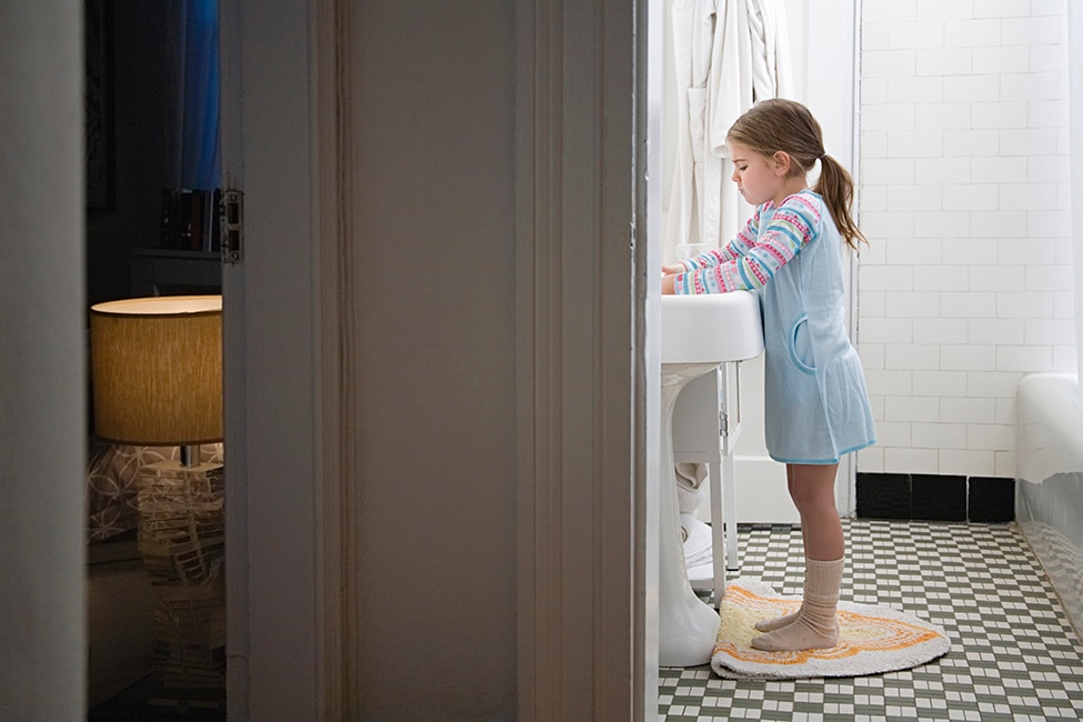 View from a hallway shows a girl washing her hands in a bathroom next to her bedroom.