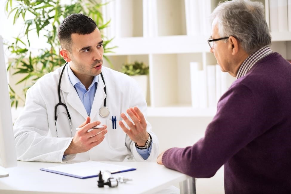A healthcare professional talking to an older patient.
