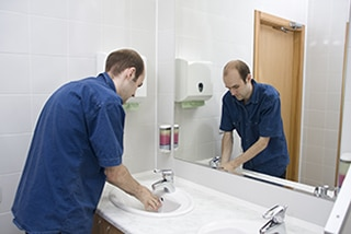 Man washing hands in sink in front of a mirror