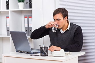 Man drinks from a large glass of water as he works on a computer.