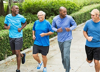 4 middle-age men wearing different shades of blue jogging down a sidewalk.