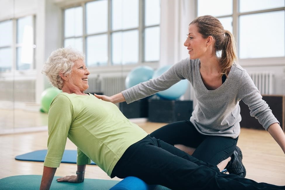 An older woman stretching while a physical therapist guides her.