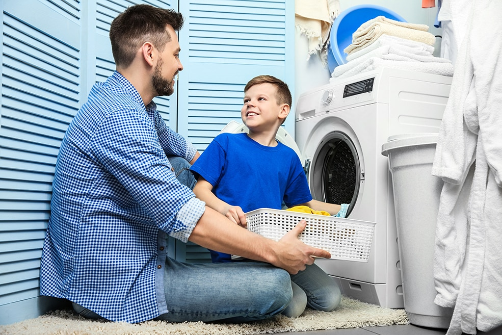 Father and son work together to put dirty laundry into a washing machine.