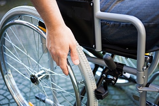 Image of someone in a wheelchair about to grip the wheel