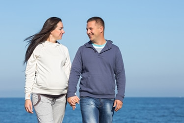A pregnant woman and her male partner walking on a beach.
