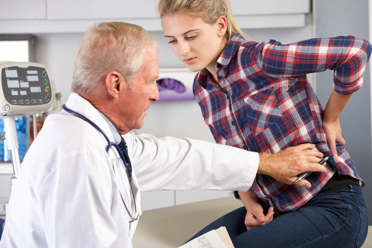 Teen girl talks to doctor and holds a hand to her lower back.