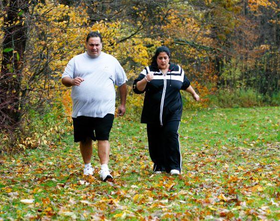 Man and woman powerwalking outdoors.